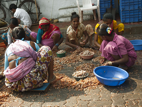 le donne e le bambini puliscono i gamberetti